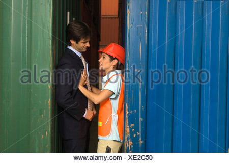 Side profile of a businessman and a female dock worker romancing between two cargo containers - Stock Photo