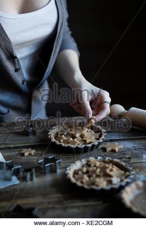 Woman decorating a tart - Stock Photo
