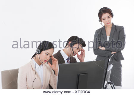 Three young stressful business people wearing headphones - Stock Photo