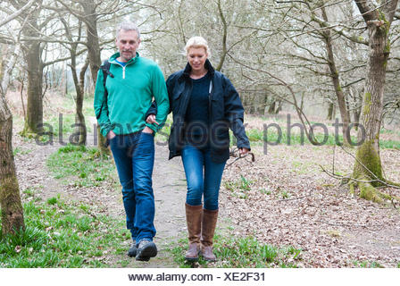 Hiking couple walking in woods - Stock Photo