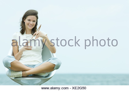 Teenage girl sitting in chair, holding chopsticks and take out food container, smiling at camera - Stock Photo