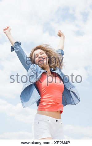 Portrait of young woman with arms raised - Stock Photo