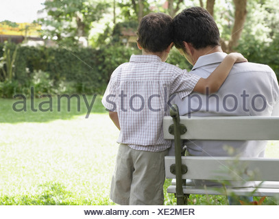 Man outdoors sitting on bench with young boy being affectionate toward him - Stock Photo