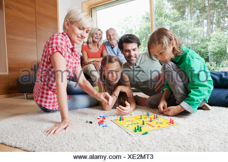 Germany, Bavaria, Nuremberg, Family playing board game together - Stock Photo