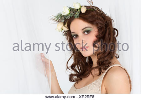 Young woman with a flower arrangement as a headdress - Stock Photo