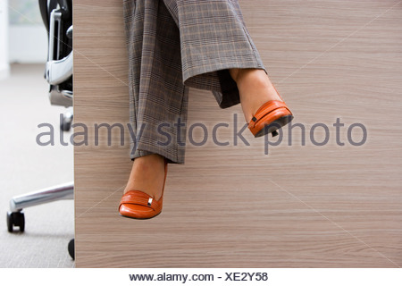 Businesswoman wearing checked grey trousers and orange high heels sitting on desk in office low section - Stock Photo
