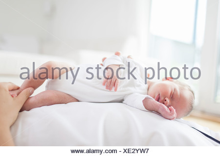 Mother holding baby's feet - Stock Photo