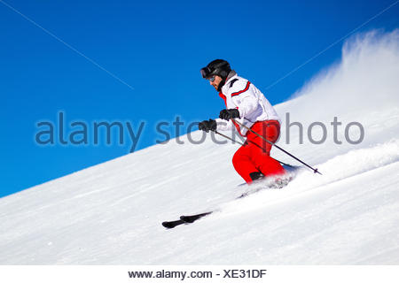 Expert male skier wearing red ski trousers skiing down a steep slope. - Stock Photo