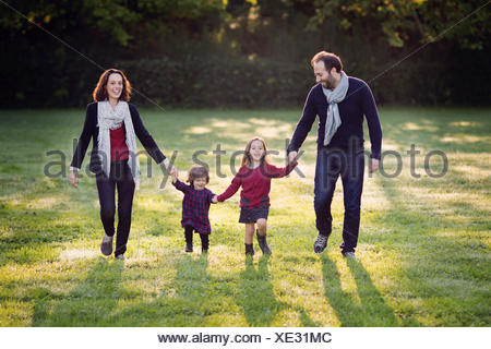 Family with two lille girls walking hand in hand on a meadow - Stock Photo