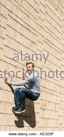 Young man doing parkour jump on brick wall, Sweden - Stock Photo