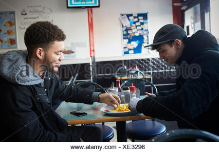 Two Male Students Eating Meal In Café - Stock Photo