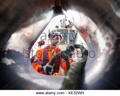 Tugboat worker pulling rope on deck - Stock Photo