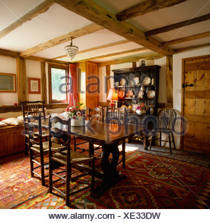 Antique ladderback chairs and wooden table in small country dining room with colourful Kelim rugs on the floor - Stock Photo