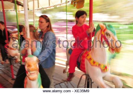 Israel, Haifa, Gan Ha'em ('the mother's garden') on the Carmel Mountain Children on a merry-go-round - Stock Photo