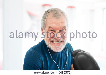 Portrait of aggressive senior man with earphones and boxing gloves in gym - Stock Photo