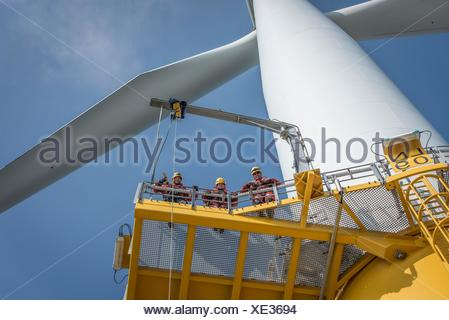 Portrait of engineers on wind turbine at offshore windfarm - Stock Photo