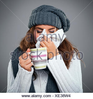 Young woman having flu and blowing her nose at handkerchief Debica, Poland - Stock Photo