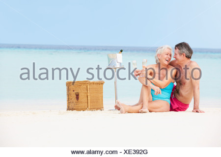 Senior Couple On Beach With Luxury Champagne Picnic - Stock Photo