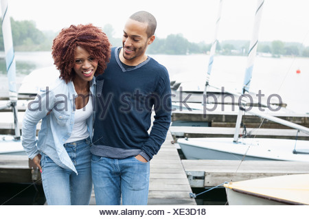 Young couple on jetty laughing - Stock Photo