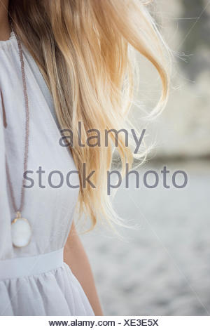 Blond woman wearing a dress and necklace on a sandy beach. - Stock Photo