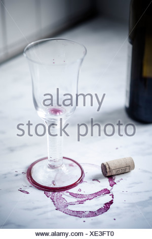Empty red wine glass, bottle, stains and wine cork on white marble - Stock Photo