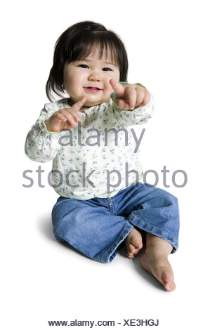 Little girl seated smiling - Stock Photo