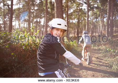 Twin brothers on BMX bikes in forest - Stock Photo