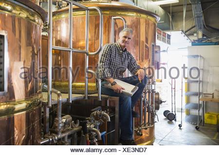 Portrait of brew master sitting at copper stills - Stock Photo