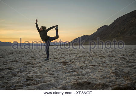 Full length of young woman doing yoga in desert at sunset, Death Valley, Nevada, USA - Stock Photo