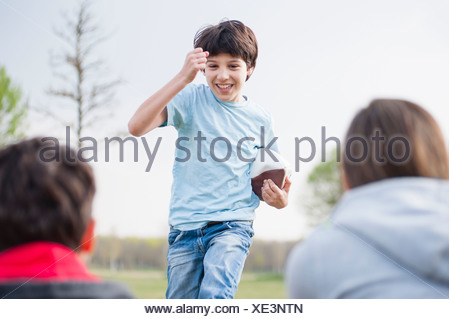 Parents watching son run with rugby ball in park - Stock Photo