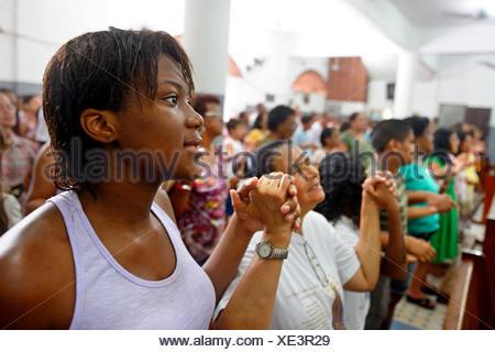 Worshippers holding each other's hands and praying, Catholic mass in a slum or favela, Jacarezinho favela, Rio de Janeiro - Stock Photo