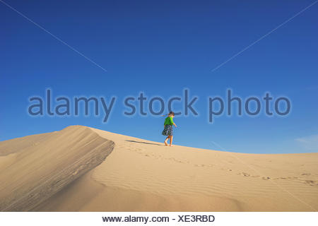 Girl running along top of a sand dune - Stock Photo