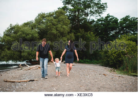 Pregnant couple strolling on beach with male toddler son, Lake Ontario, Canada - Stock Photo
