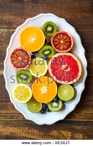 Plate of blueberries, kiwis and sliced citrus fruits on wood - Stock Photo