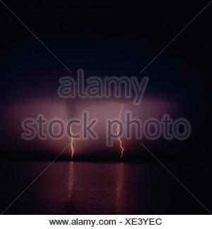 Lightning flickering in sky at night - Stock Photo