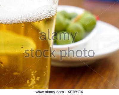 Pint of beer served with olives - Stock Photo