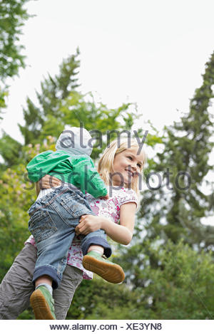 Young blonde girl carrying baby brother - Stock Photo