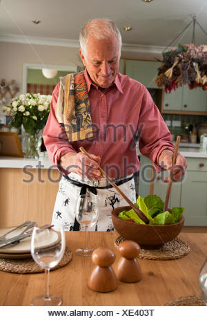 Senior man preparing salad in kitchen - Stock Photo