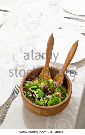 Close-up of salad in a bowl on the set table - Stock Photo