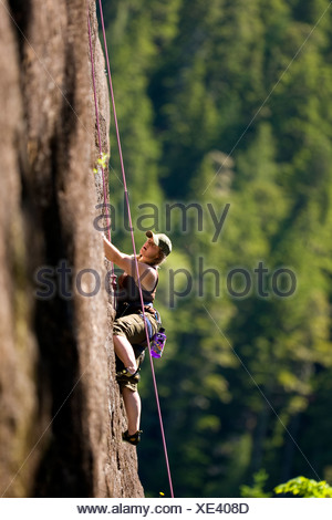 Female rock climber on Red Earth (5.9) Main Wall Crest Craigs in Strathcona Park.  Vancouver Island, British Columbia, Canada - Stock Photo