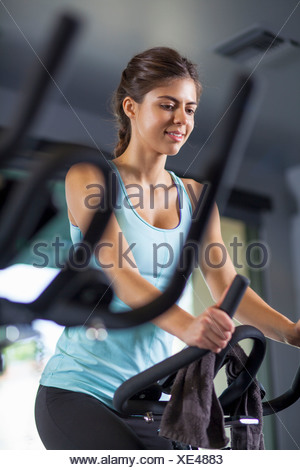 Young woman on cross-trainer - Stock Photo