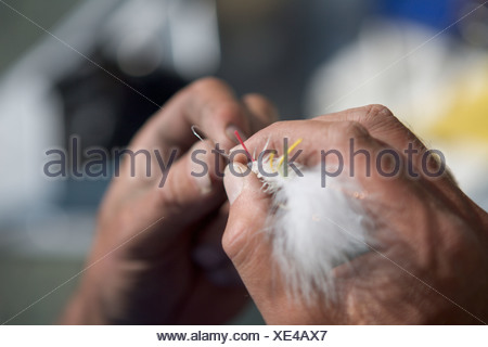 A close-up view of hands tying a fly to fishing line. - Stock Photo