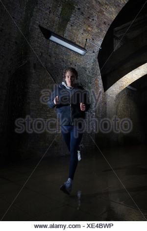 Young man jogging through urban tunnel at night - Stock Photo
