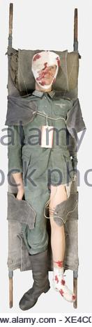 WEHRMACHT, Soldat blessé de la Wehrmacht, sur mannequin, comprenant une veste de combat quatre poches en treillis vert roseau, montée en sous-officier des transmissions avec ses boutons, aigle de poitrine, étiquette de blessure et épaulettes à liseré marron clair, un pantalon de combat en treillis vert roseau avec une seule jambe. Joint une botte troupe en cuir noir. Présenté sur un brancard réglementaire allemand, , - Stock Photo