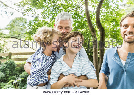 Mature man with grandsons sitting on his lap in garden - Stock Photo