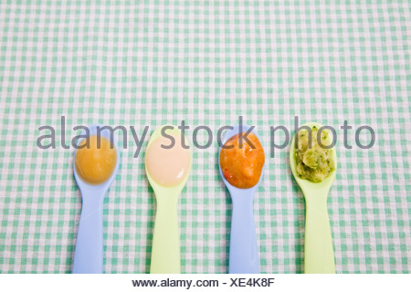 Baby food on spoons - Stock Photo