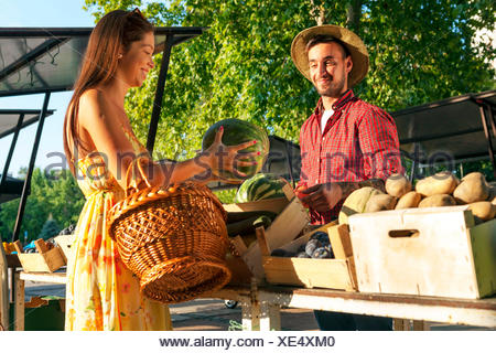 Young man selling fruit and vegetables at market stall - Stock Photo