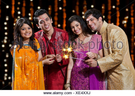Portrait of friends playing with firecrackers - Stock Photo