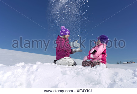 Two young girls playing in snow - Stock Photo