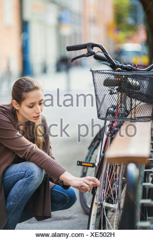 Young woman crouching while repairing bicycle - Stock Photo